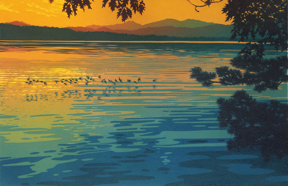 Birds skim the surface of a lake at sunset.