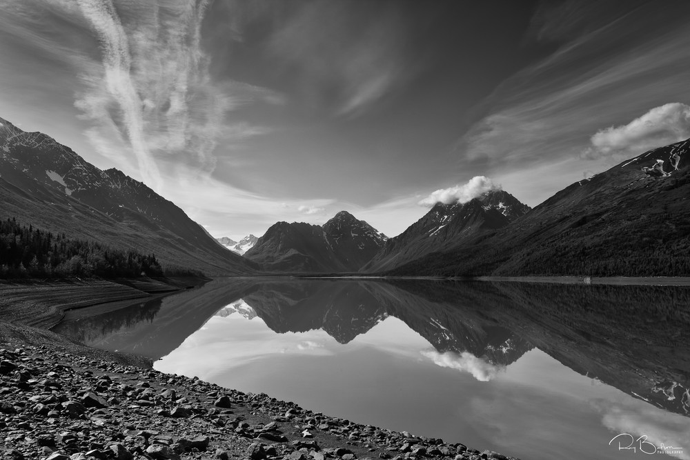 Reflection of The Mitre mountain, Bold Peak and other Chugach Mountains on the southeast end of Eklutna Lake in Chugach State Park in Southcentral Alaska. Morning. Summer.