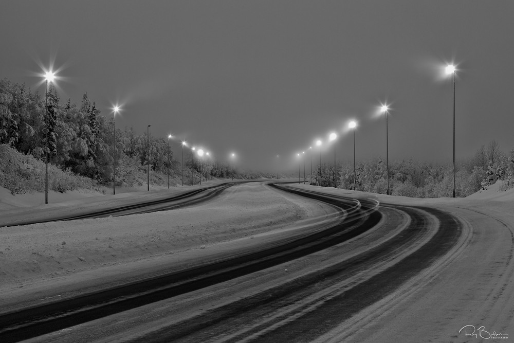 Slow shutter speed captures stoplights of cars as a blur on a cold, foggy winter morning along the Eagle River Loop Road in Southcentral Alaska.