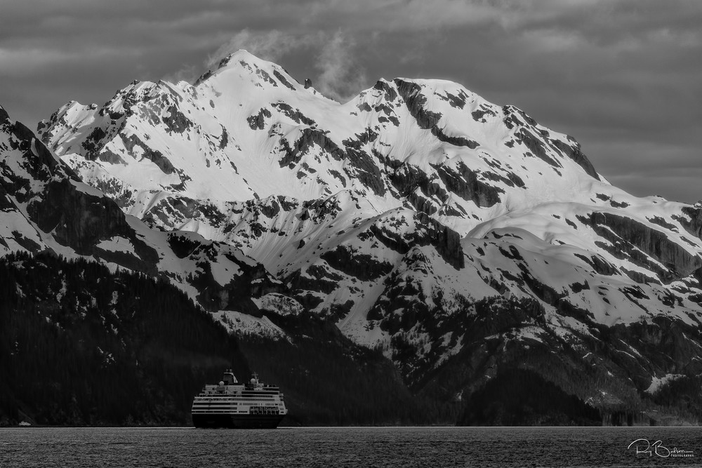 A cruise ship heads out of Resurrection Bay with the Resurrection Mountains in the background as it departs Seward and the Kenai Peninsula in the evening in Southcentral Alaska. Spring.
