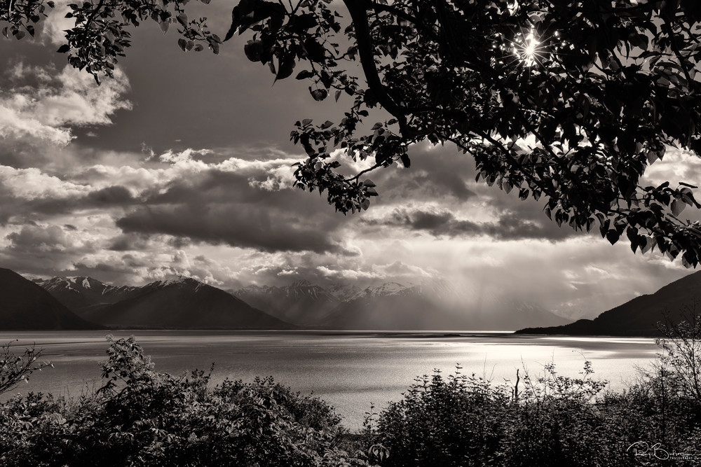 Storm clouds loom over the Chugach Mountains across Turnagain Arm from Hope in Southcentral Alaska. Spring. Morning.