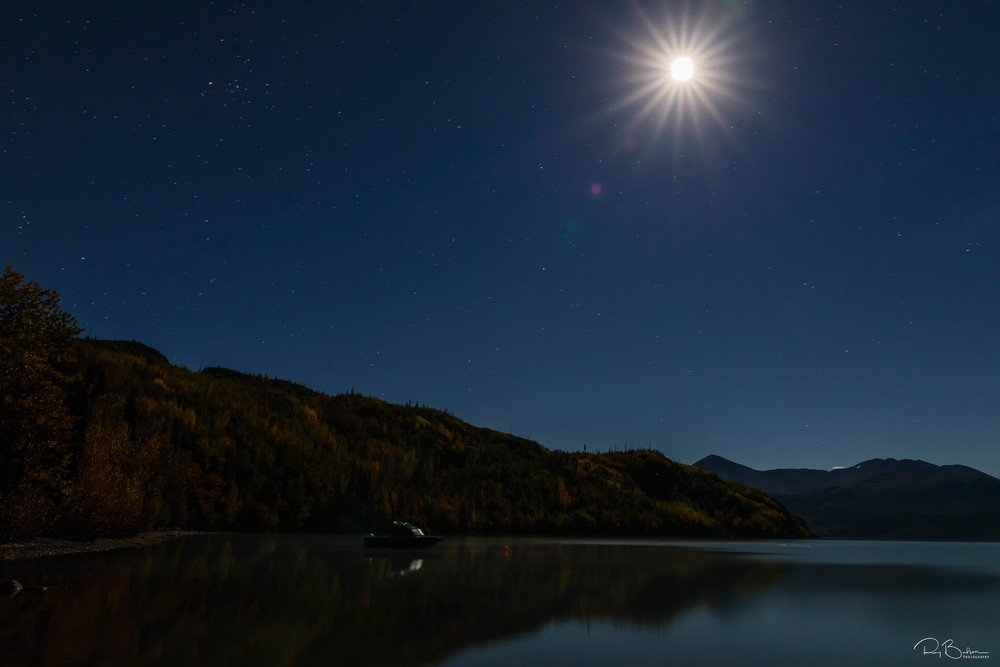Fishing boat on Skilak Lake bathed in moonlight in the Kenai National Wildlife Refuge in Southcentral Alaska. Autumn. Evening.