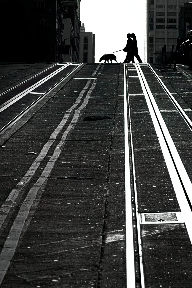 Graphic high contrast B&W image of street car rails leading up a hill to people and a dog crossing the street in San Francisco, CA