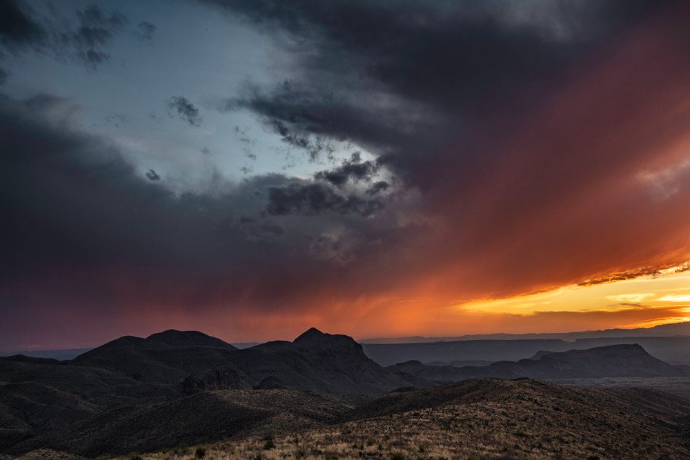 Standing in Big Bend National Park looking across at a storm and sun setting in both countries.