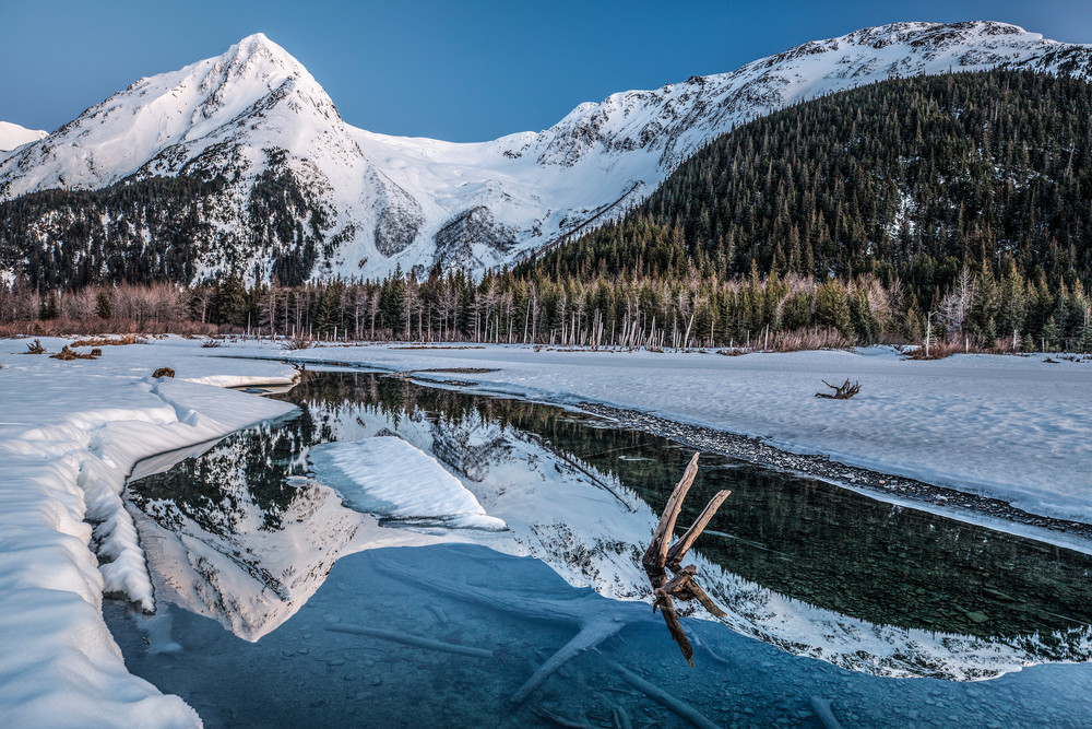 Spring landscape view of ice and open creek with snow-covered Chugach Mountains & Explorer glacier reflection in Portage Valley  April 2017  Photo by Jeff Schultz/SchultzPhoto.com  (C) 2017  ALL RIGHTS RESERVED