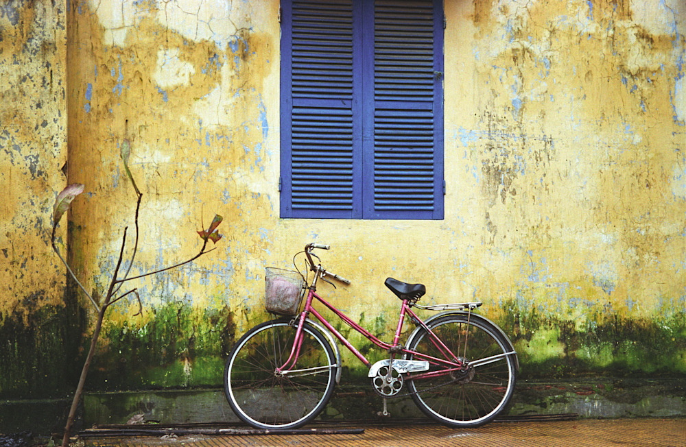 Bicycle Under Blue Shutter in French Vietnam under a Yellow Wall