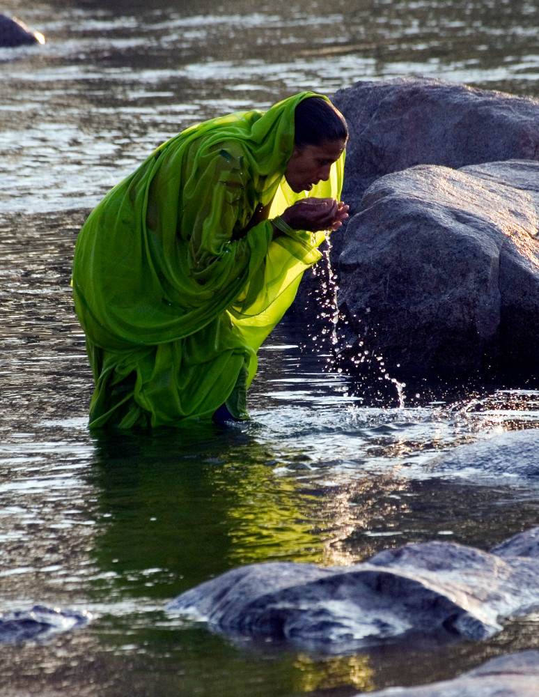 Woman bathing in river in Orchha India