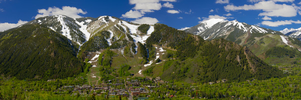 mountain light images, spring view of aspen town and ski area in colorado. Snow on the mountain melts into green spring grasses