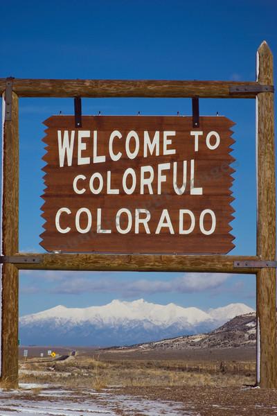 mountain light images colorado new mexico border welcome sign with the sangre de cristo mountains seen through it