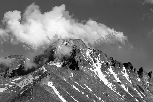 mountain light images the summit of longs peak with clouds blowing over a striking black and white image