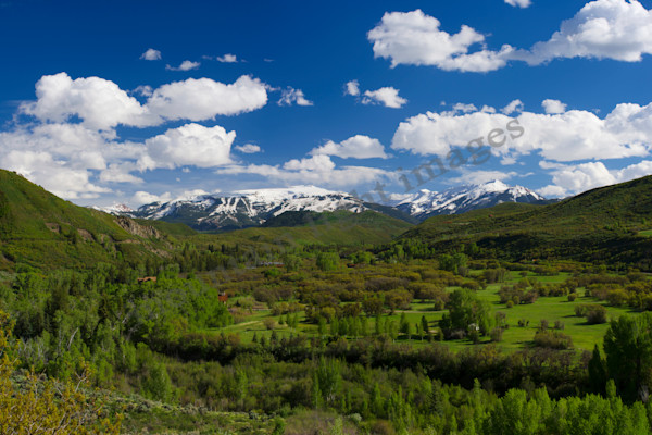 mountain light images snowmass ski area from watson divide may sunny day with clouds snow and green valley
