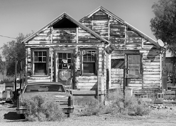 a house with an old lincoln in front in baker, california