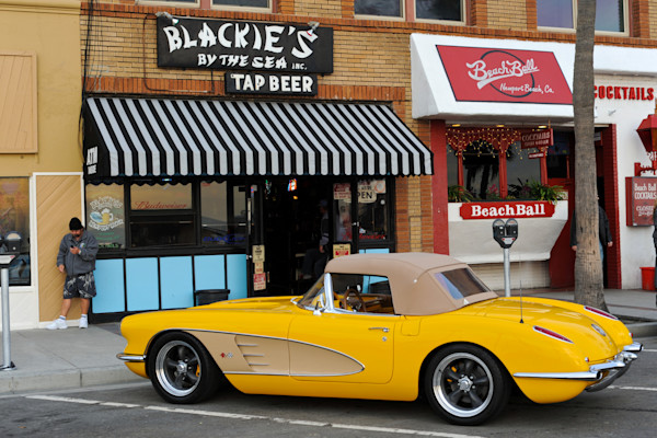 a 1962 yellow corvette in front of blackie`s, newport beach