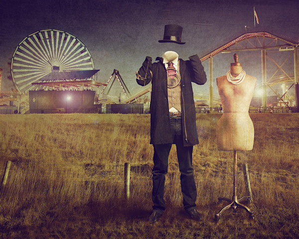 An quirky little scene with a mannequin and what looks like the invisible man posed in front of an amusement park in this digital image by Kim Whittemore.
