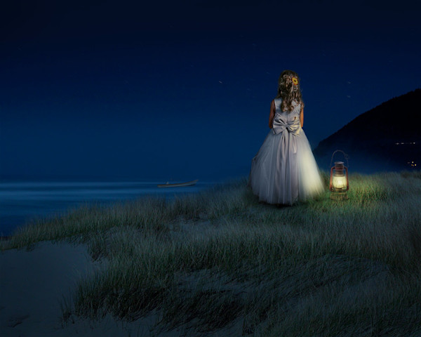 A young girl in a party dress stands alone on a beach and gazes out to sea in this digital image by Kim Whittemore.