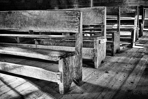 A row of rustic pews in an old church are featured in this black & white print by photographer Todd McPhetridge.