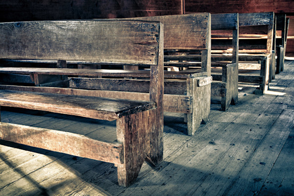 Faded gray and brown pews line up silently in an old church in this print by photographer Todd McPhetridge.