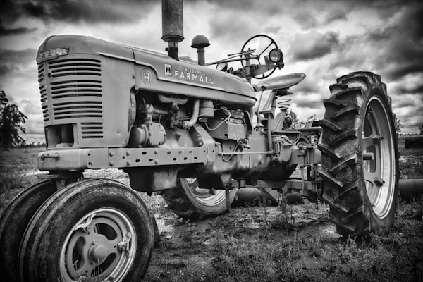 An old farm tractor sits in a field in this print from a photograph by Todd McPhetridge.