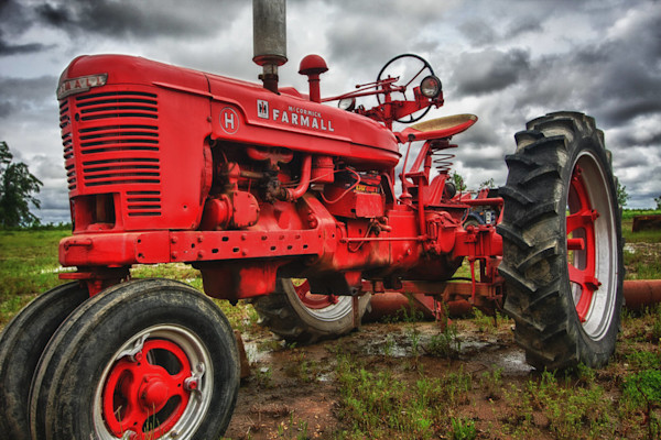 An old bright red tractor sits patiently waiting under a stormy sky in this Open Edition print by photographer Todd McPhetridge.