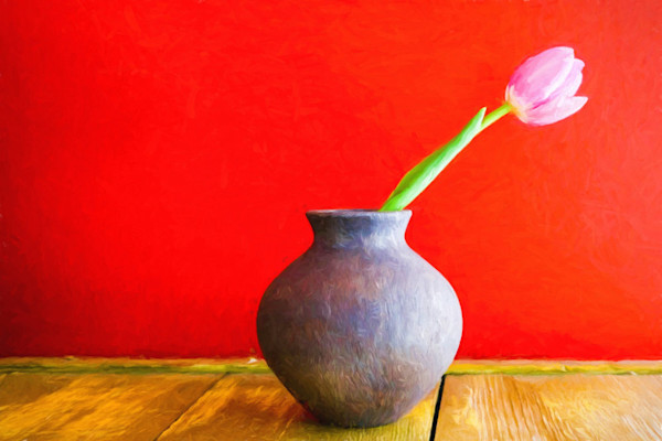 A single pink tulip leans out over the edge of its blue earthen vase, stark against a vivid red background in this Open Edition print by photographer Todd McPhetridge.