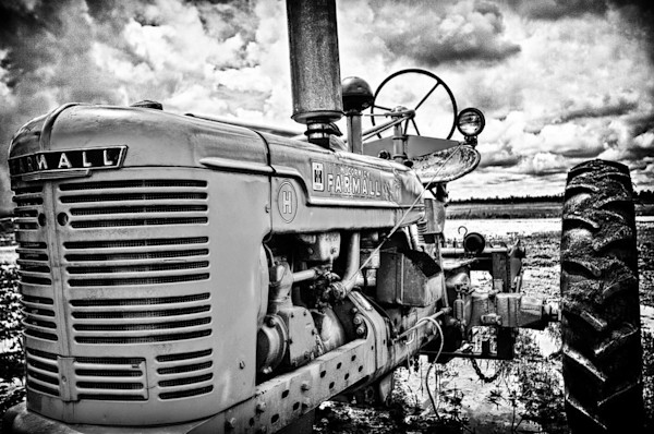 In this black & white image, an old farm tractor sits alone under a threatening sky in this Open Edition print by photographer Todd McPhetridge.