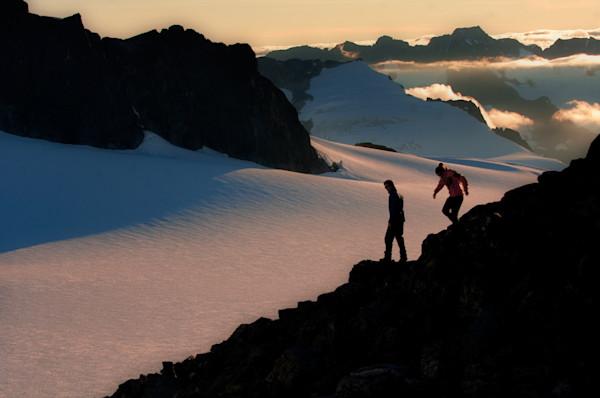 A couple enjoys the endless mountain views high up on a rocky ridge in the Coastal Range, Southeast Alaska.