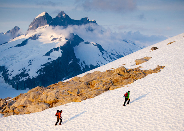 Two backpackers trek up a steep snowy mountain in the heart of Alaskas Coastal Range
