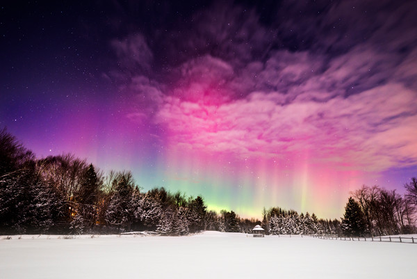 Moonlight Aurora, moon shines on a winter field while aurora borealis peeks through the clouds
