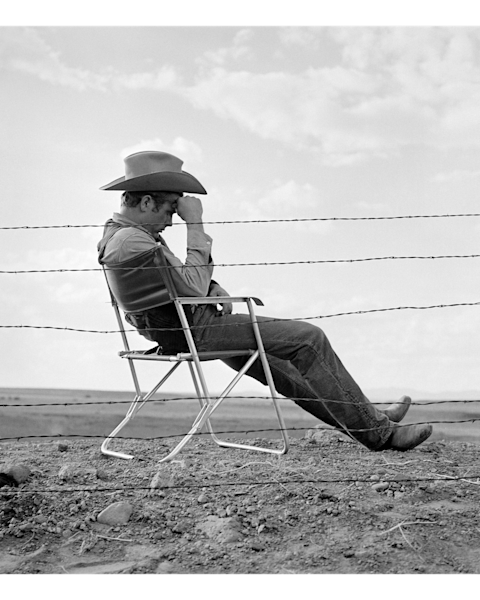 James Dean sitting behind a fence on the set of Giant.