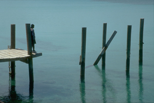 A boy stands at the end of a collapsed pier on the Carribean island of Eluthera.
