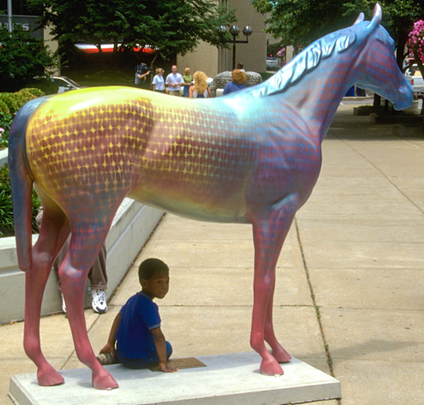 Boy sits in the shade of a painted horse (Horse Mania).