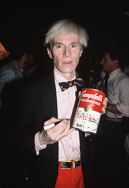 Andy Warhol with a campbells soup can