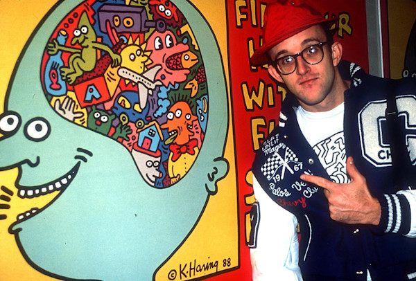 Keith Haring pointing at a paintings