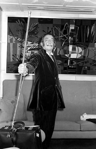 Salvador Dali with his cane and a painting