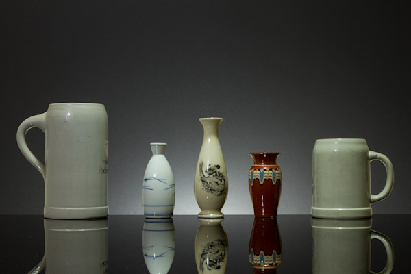 A Fine Art Photograph of Vases and Mugs With Reflections on Black Plexi by Michael Pucciarelli