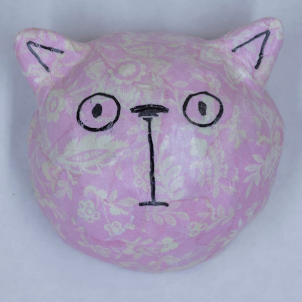 Buy a pink paper mache cat face for a fun wall in your home.
