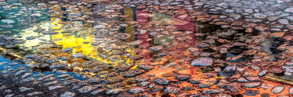 Colorful reflection in puddle on cobblestone street