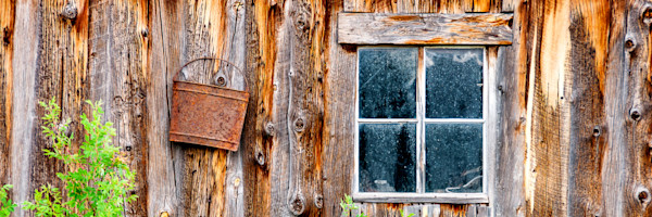 Art photograph, panorama of old bluish window on rustic brown barn