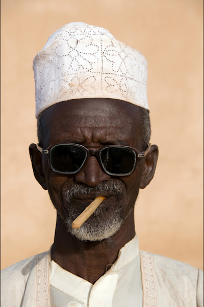 Muslim man with cap on and sunglasses chewing stick