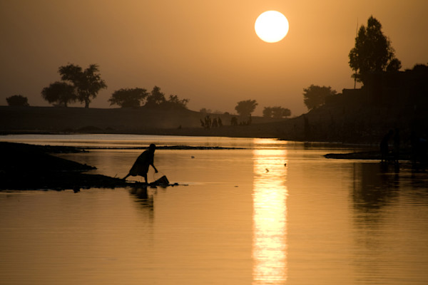 Fine art photograph of a silhouette of woman with bucket by Bani river at sunset