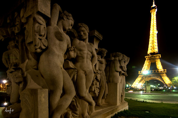 Statue of men and women at night with Eiffel tower lit up behind, in fine artphotograph