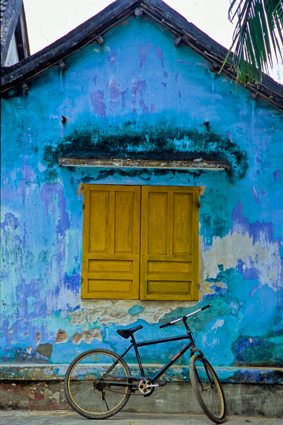 Bike in front of teal wall with mustard window