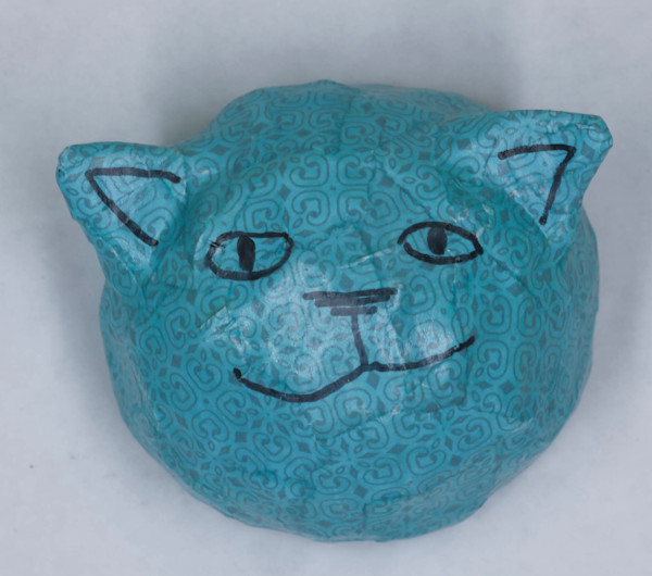 Buy a teal smiling paper mache cat face for a fun wall in your home.