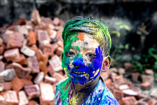 Portrait of young boy covered in Holi colors, in a fine art photograph print