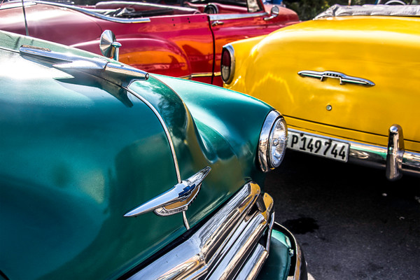 Fine art photograph of Red, yellow and green classic cars in partial view together