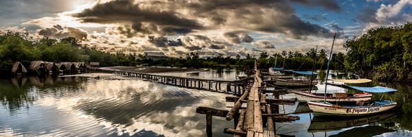 Panorama photograph art of wooden walkway by boats in eastern Cuba