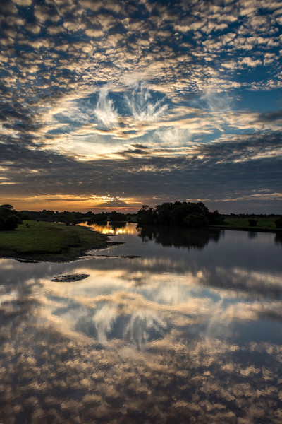 Surreal cloud formation mirrored in pond