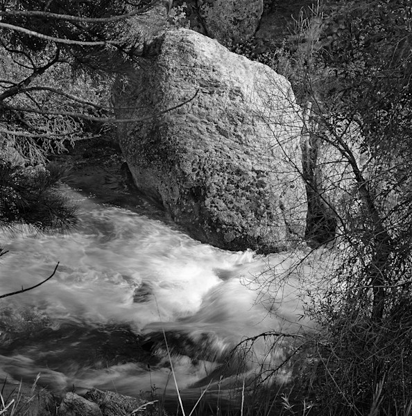 Masterful black & white fine art photograph of a stately old stone standing up to the rushing water of a Colorado stream.