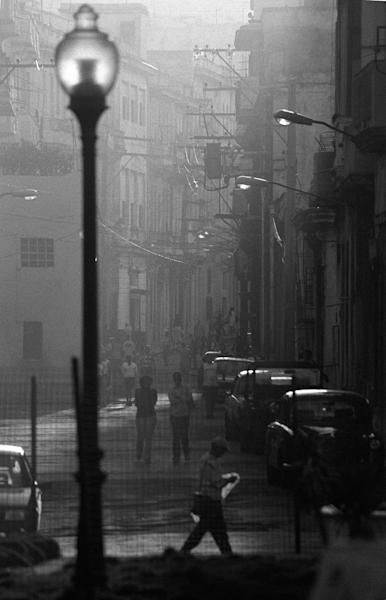 Man walking in afternoon sun in Havana, Cuba with street lamp light in black & white