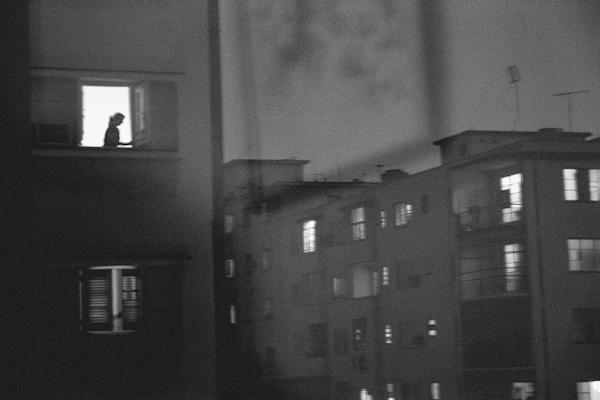 Woman in window at night in Havana, Cuba apartments